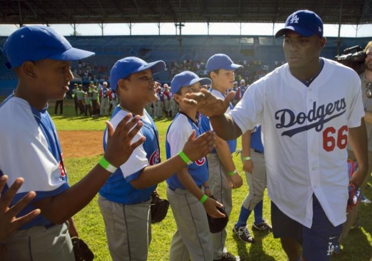El jugador de los Dodgers de Los Ángeles, Yasiel Puig, de Cuba, saluda a jóvenes jugadores de béisbol antes de impartir un curso práctico en La Habana.