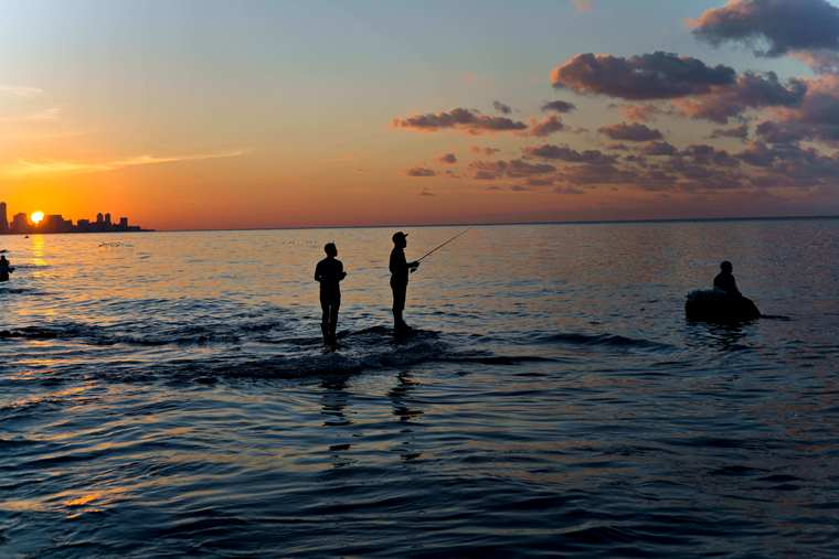 Fishermen stand in the water as a man on a foam raft fishes for bait, off Chivo beach in Havana, Cuba. (AP image)