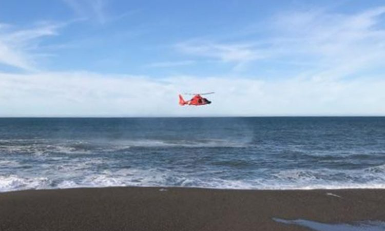 In this photo a U.S. Coast Guard helicopter searches a beach where a father and his young son were swept out to sea. (AP Image)