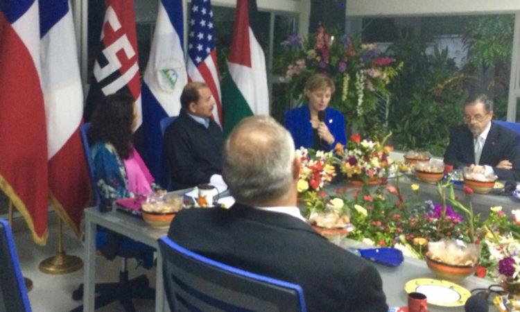 Embajadora Dogu sentada en una mesa junto al Presidente Ortega