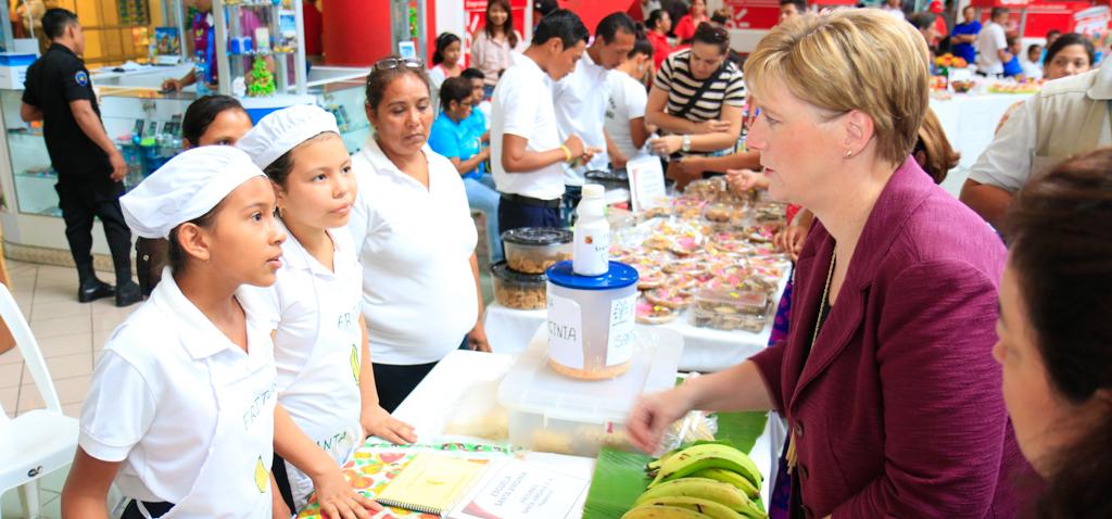 Ambassador Dogu talking to 2 kids and a lady at the fair