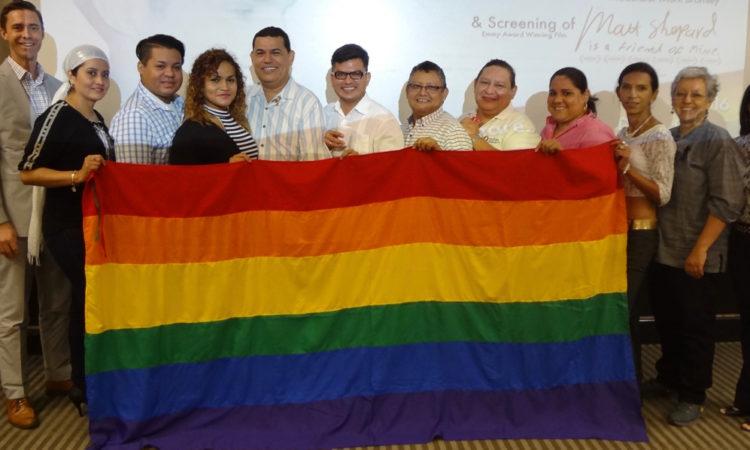 foto de grupo con la bandera del arco iris