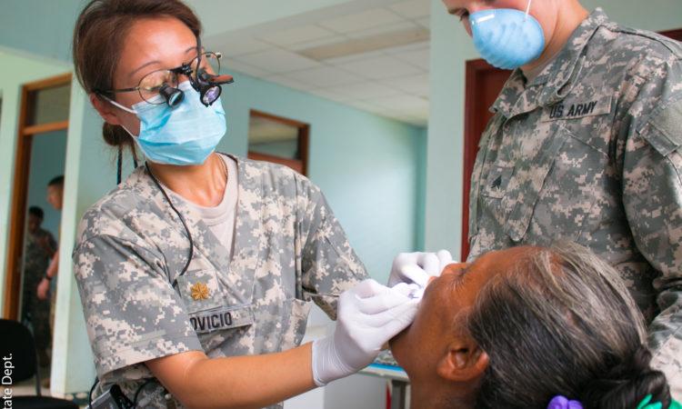Dentista militar y asistente examinan a una paciente