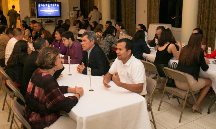 mucha gente sentada en mesas largas conversando