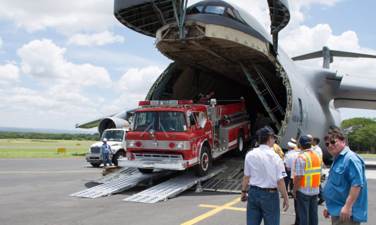 camión de bomberos rojo sale de las entrañas de un avión
