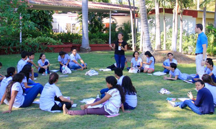Estudiantes sentados en la grama en un círuculo escuhando a uno de ellos hablar