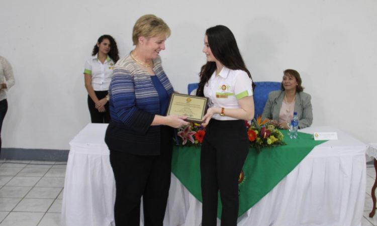 Embajadora recibiendo reconocimiento de joven
