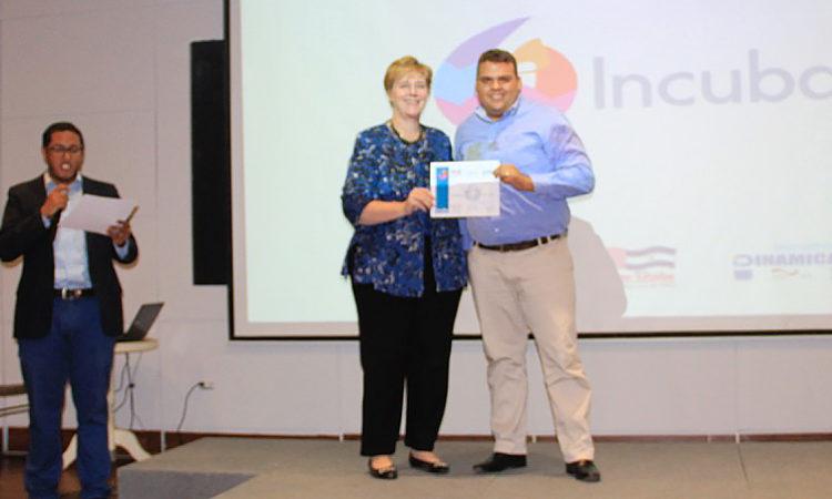 La Embajadora Dogu posa para una foto junto a un hombre con su certificado