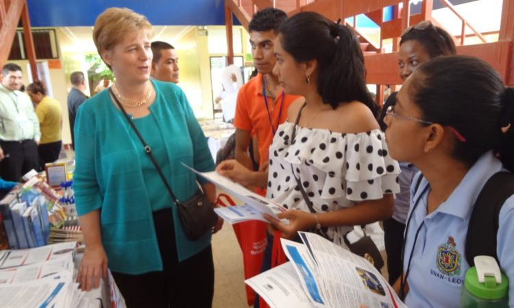 Ambassador Dogu talking to two ladies holding brochures in their hands