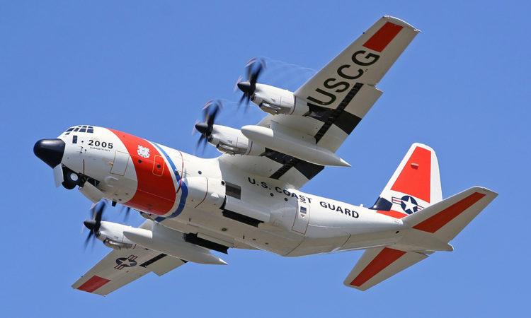 Avión blanco con rayas anaranjadas grande de carga de cuatro motores