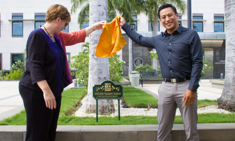 Ambassador Dogu together with Mark Saavedra lifting a yeloow cover to unveil a green plaque