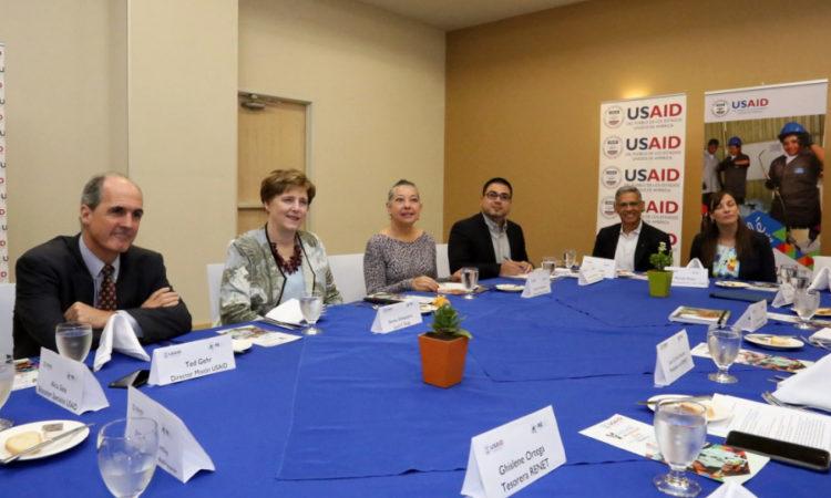 grupo de gente sentados alrededor de una mesa en discusión de un tema