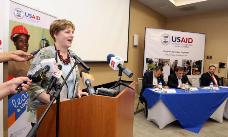 La embajadora tras el podio hablando durante su discurso
