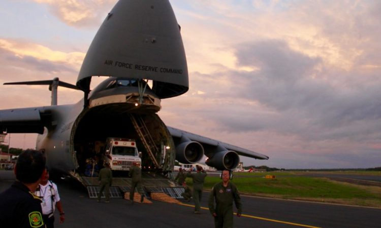 A donated ambulance is driven out of the cavernous cargo compartment of the C-5 Galaxy