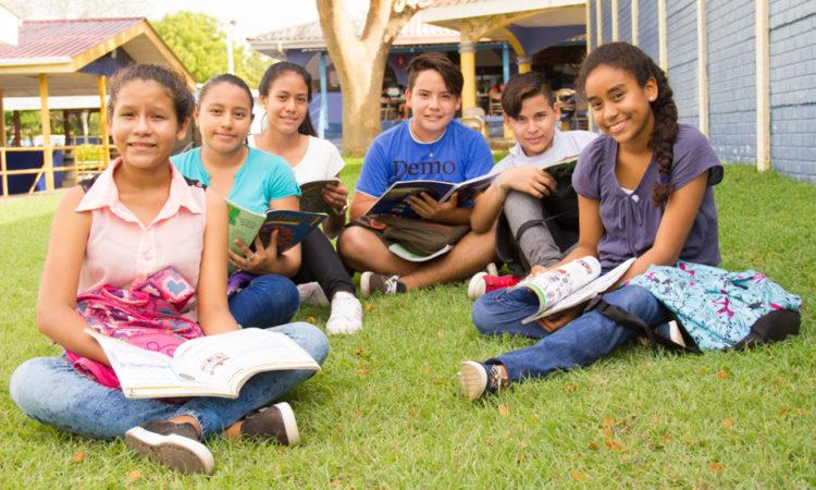 Grupo de jóvenes estudiantes sentados en el suelo