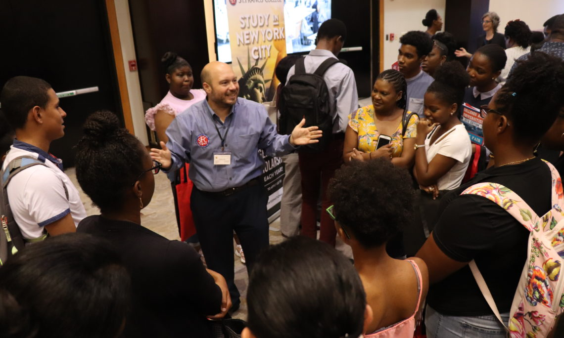 Students surround a representative from St. Francis College, New York at the Embassy's College Fair 2019 at the Hyatt Regency, POS.