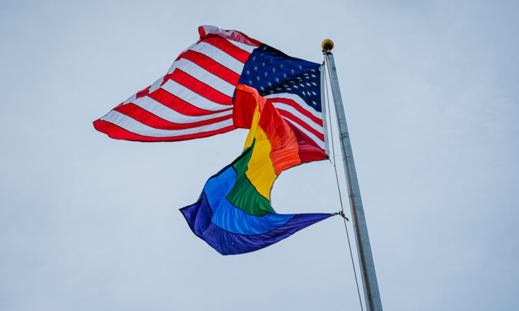 LGBTQ Flag flying with the American Flag