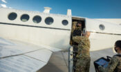 military people unloading a plane