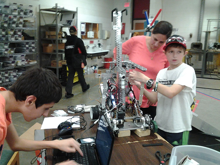 Nolan Kuza and Joshua Miller with Kelley O'Rourke (Mentor), checking the connection between software and motors. Photo Credit: Carolyn Campbell.
