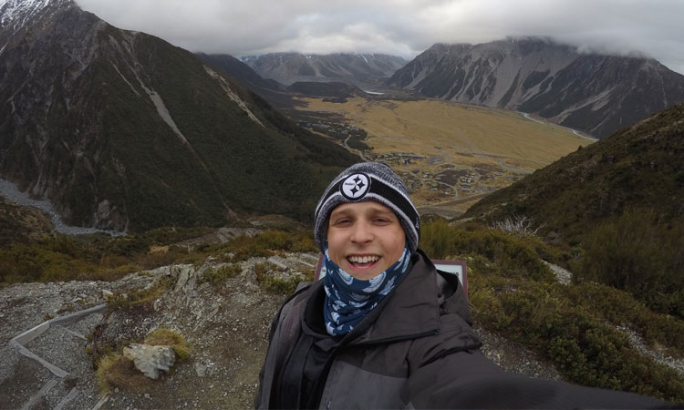 Zeesha at the top of a trail overlooking the cloud covered peak of Mount Cook (Photo Credit: Zeesha Braslawsce).