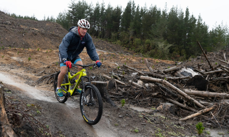 "Ambassador Brown braved the freezing rain took to the scenic slopes of the Whakarewarewa Redwood Forest, taking on the ""Split Enz"" mountain bike track. Photo credit: U.S. Department of State."