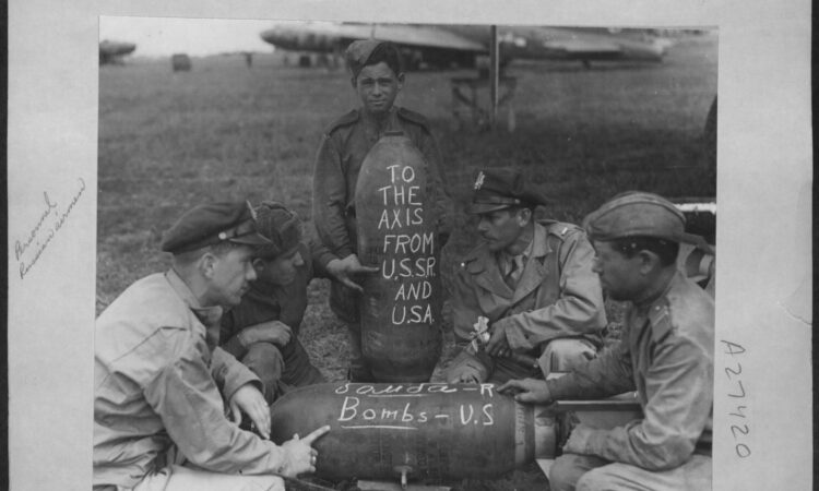 "Lt. Lester D. Poehner of Ohio and Lt. Albert Hunt of Pennsylvania talk with three Soviet soldiers. The word for ""bomb"" is written in both English and Russian on a 250-pound general purpose demolition bomb."