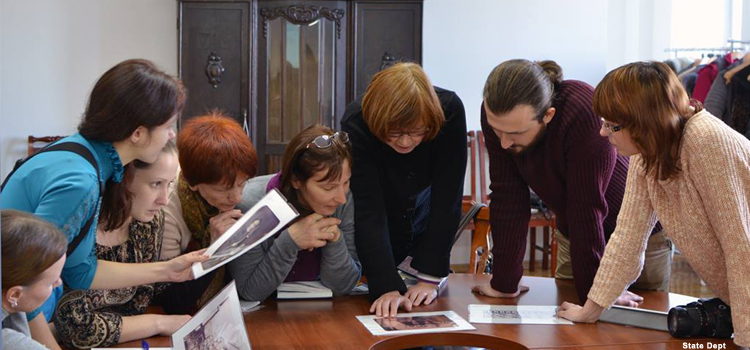 Group of people sit at a table, study handouts (Photo by State Dept)