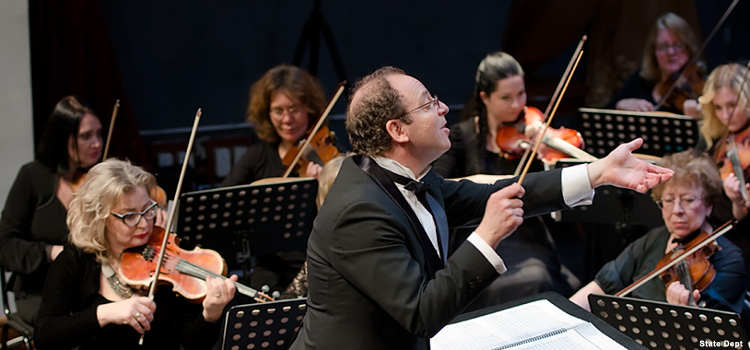 Man conducts an orchestra (Photo by State Dept)