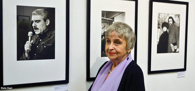 Woman stands in front of displayed photos.