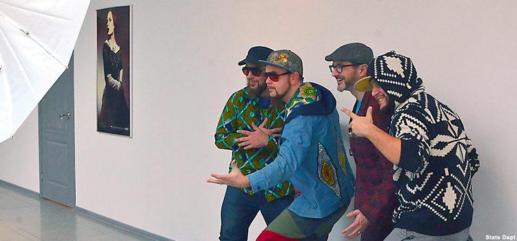 Four men pose for a photo.