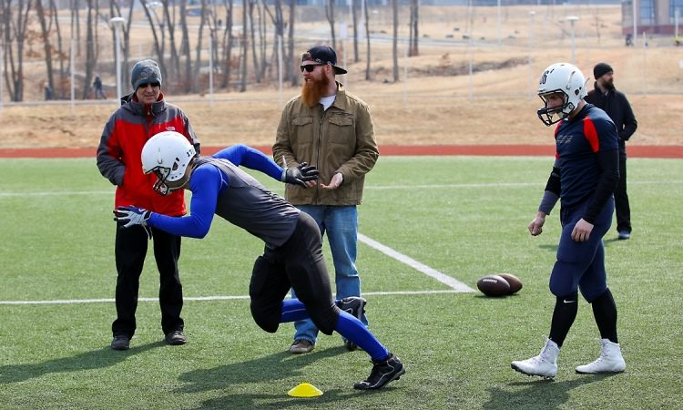 Three men stand, watch football player run (Photo by State Dept).