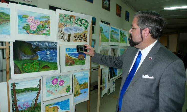 Man takes photos of children's drawings (Photo by State Dept)
