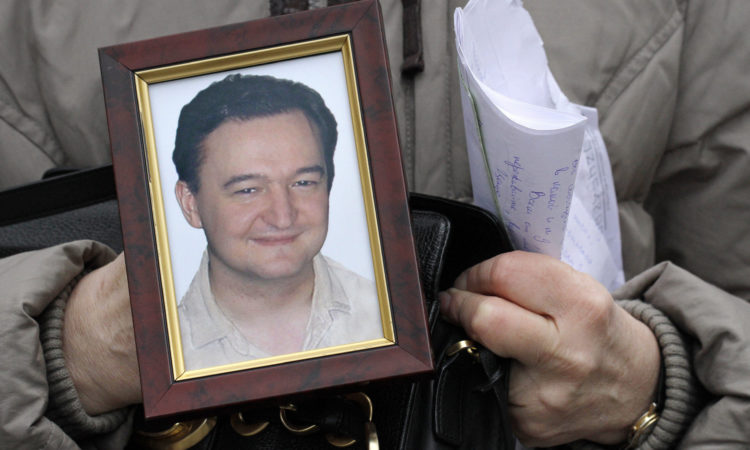Nov. 30, 2009, file photo a portrait of lawyer Sergei Magnitsky who died in jail, is held by his mother Nataliya Magnitskaya, as she speaks during an interview with the AP in Moscow. (AP Photo/Alexander Zemlianichenko, File)