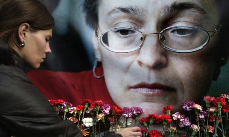 Женщина кладет цветы к портрету убитой российской журналистки Анны Политковской. AP Photo