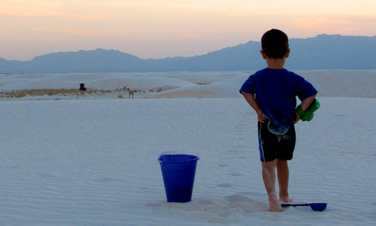 Minor next to a sand bucket on top of the white gypsum sand.