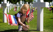 Child attends a grave at Margraten cemetery