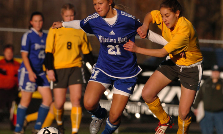Wheeling Park defender Arlene Wheeler (21) holds off Huntington forward Aly Shattls during the girls' semi-final match of the West Virginia State Soccer Tournament in Beckley, W.Va., on Friday, Nov. 5, 2004. (AP Photo/Jon C. Hancock)