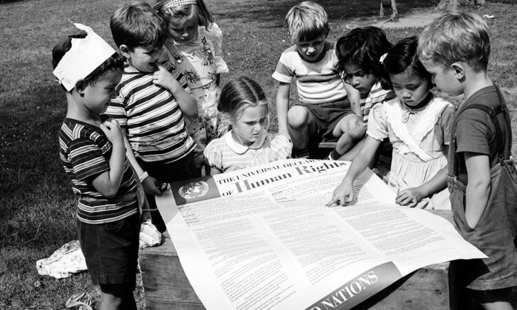 Children gathered around a large report that is titled human rights report