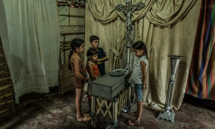 Children view the body of their 17-month-old cousin, Kenyerber Aquino Merchán, who died of severe malnutrition in Venezuela. (© Meridith Kohut/New York Times/Redux)