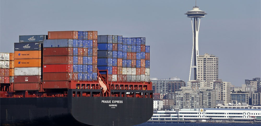 Ship carrying cargo containers with city skyline in background (AP Images)