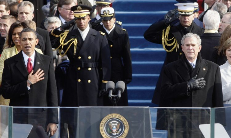 President Barack Obama, left, and former President George W. Bush sing the national anthem after Obama was sworn in to office January 20, 2009