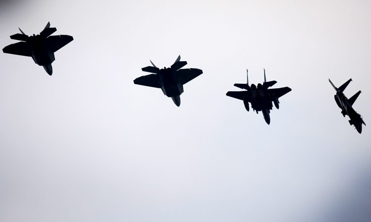 F-22 raptor aircraft in silhouette against the sky