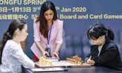 Chess referee Shohreh Bayat (center) fears returning to Iran after photos showed her appearing not to wear the regime's mandatory hijab during a tournament in Shanghai on January 11. (© Stringer/AFP/Getty Images)
