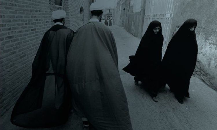 Two veiled Iranian women walk past two Iranian men