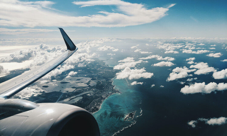 Plane wing flying over a coastline