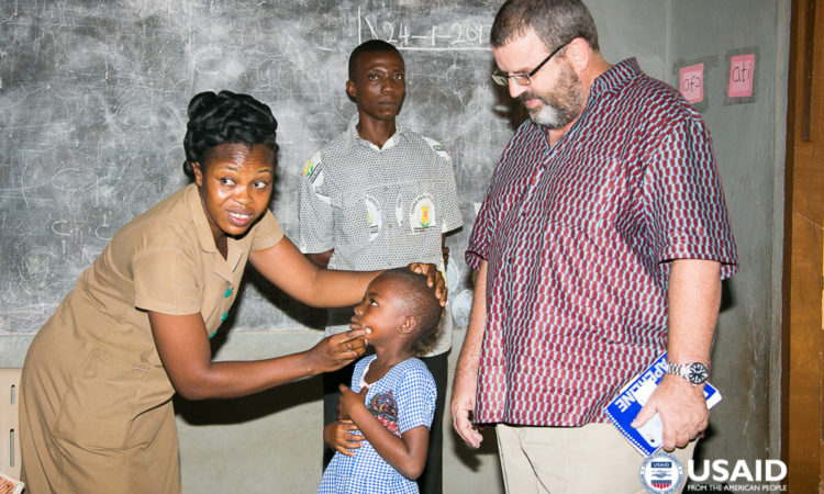USAID/Ghana Mission Director Andy Karas observes a school health examination conducted by students from the USAID-supported Community Health Nurses Training College.