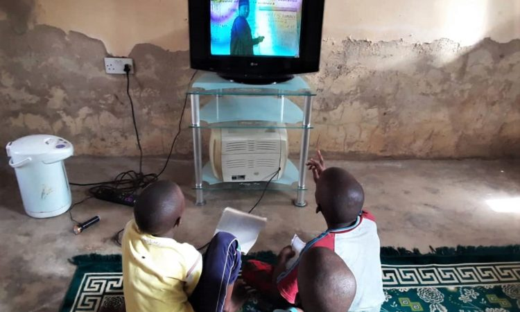 Family members of Yusuf Dahiru of Alkaleri District, Bauchi, taking in a lesson over the television this week. Photo: USAID/NEI Plus