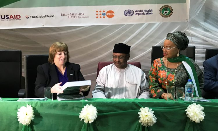 U.S. Chargé d'affaires Kathleen FitzGibbon (left) examines the U.S.-supported 2018 National Demographic and Health Survey with Minister of Health Dr. Osagie Ehanire (center) and National Population Commission Acting Chairman Barrister Abimbola Salu Hundeyin (right) at the launch ceremony for the document on November 5, 2019.