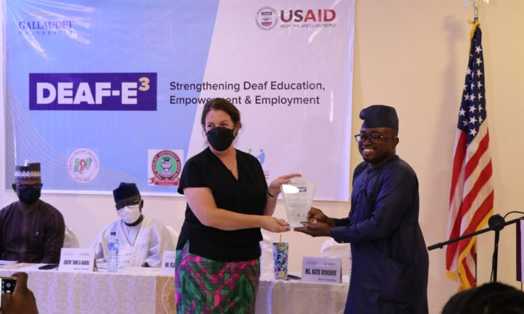 USAID Acting Mission Director Katie Donohoe receives an award of recognition from Olufemi Ige, an alumnus of Gallaudet University Alumnus and the Deaf-E3 Activity In Country Project Manager.