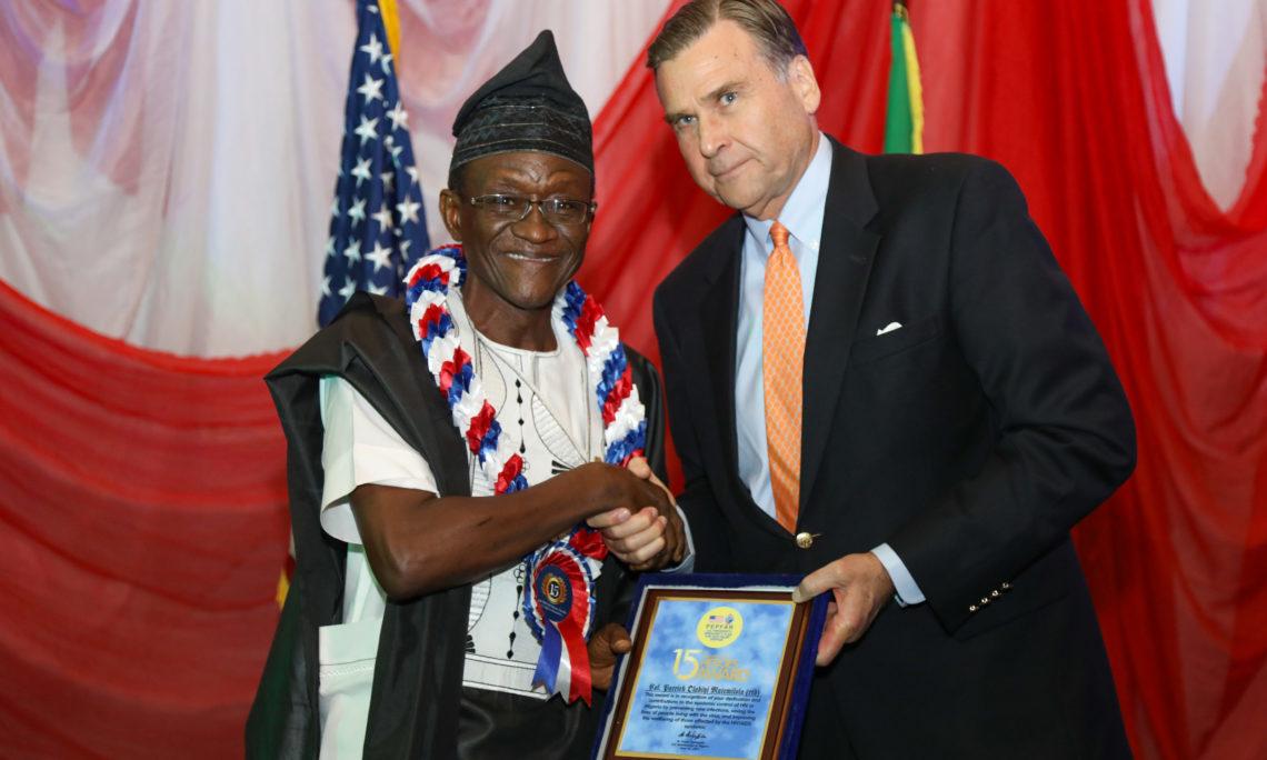 Dr Patrick Matemilola receives his PEPFAR Hero Award from US Ambassador W Stuart Symington